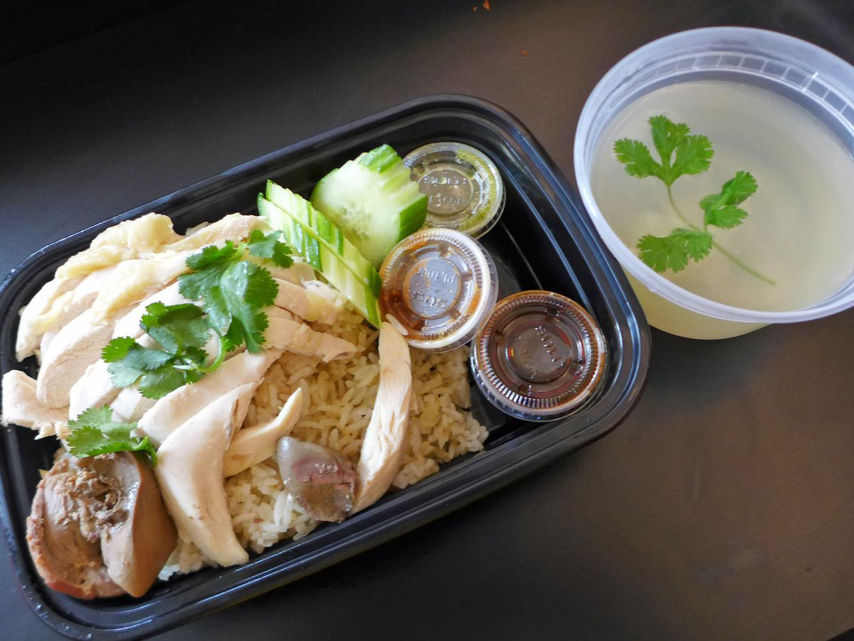 A black plastic tray with poached chicken and cucumbers on a very dark background, a plastic container of soup on the side.
