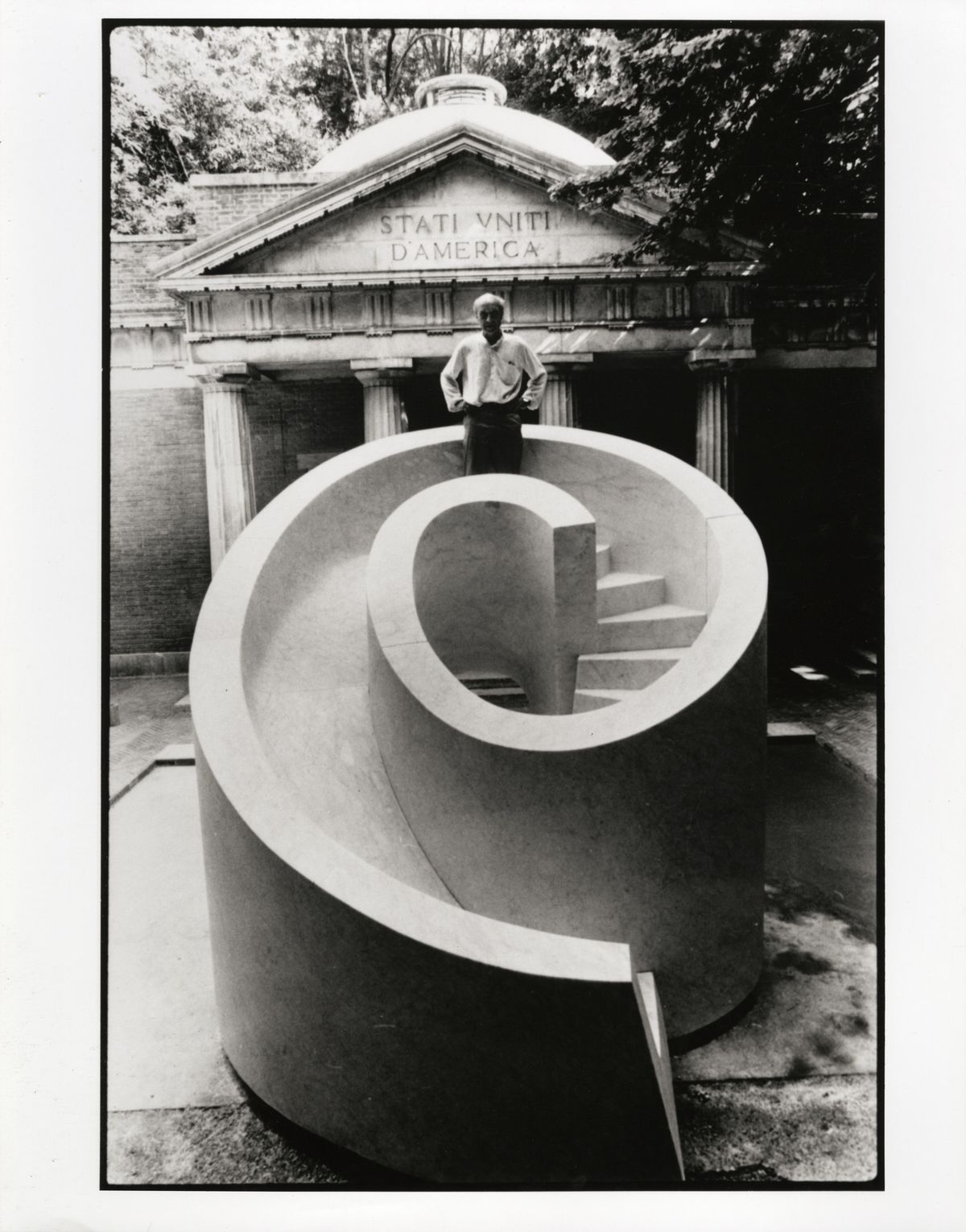 Black and white photo of man standing on top of a sculptural marble slide.