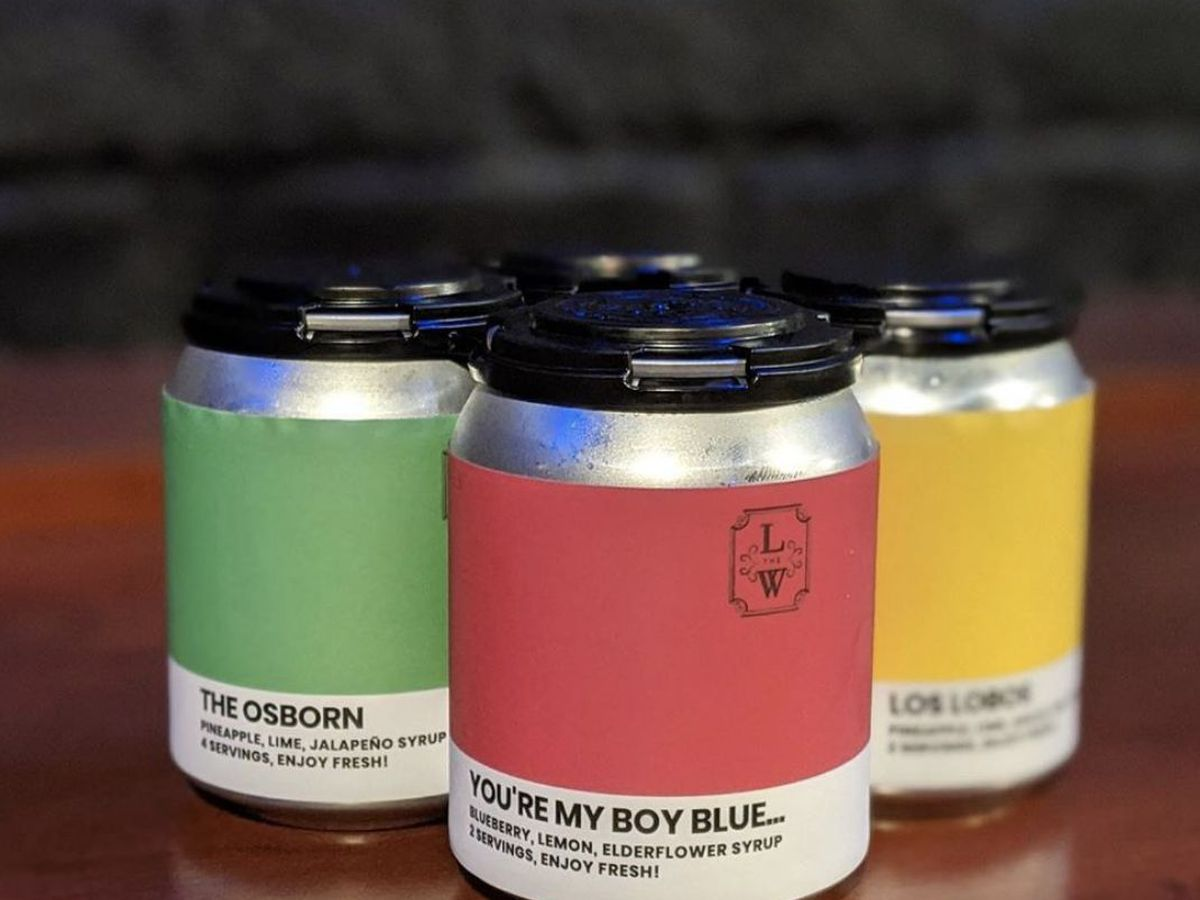 A four-pack of canned cocktails from the Last Word. The three in view each have a different label: The one on the left is green, the one in the middle is red, and the one on the right is yellow.