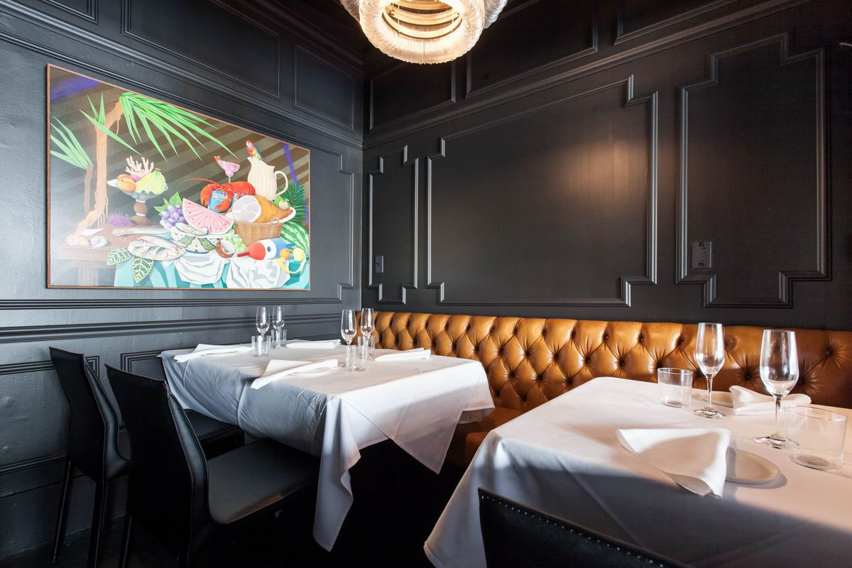 A corner of the dining room in Mexican tasting-menu restaurant Californios in San Francisco, with a yellow banquette against the black wall, white table-clothed tables, and seats, with a colorful painting on the wall