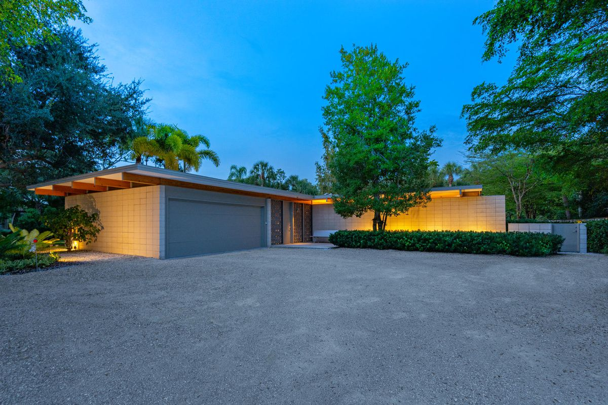 An evening shot of the exterior of a ranch midcentury modern with a long driveway in front.