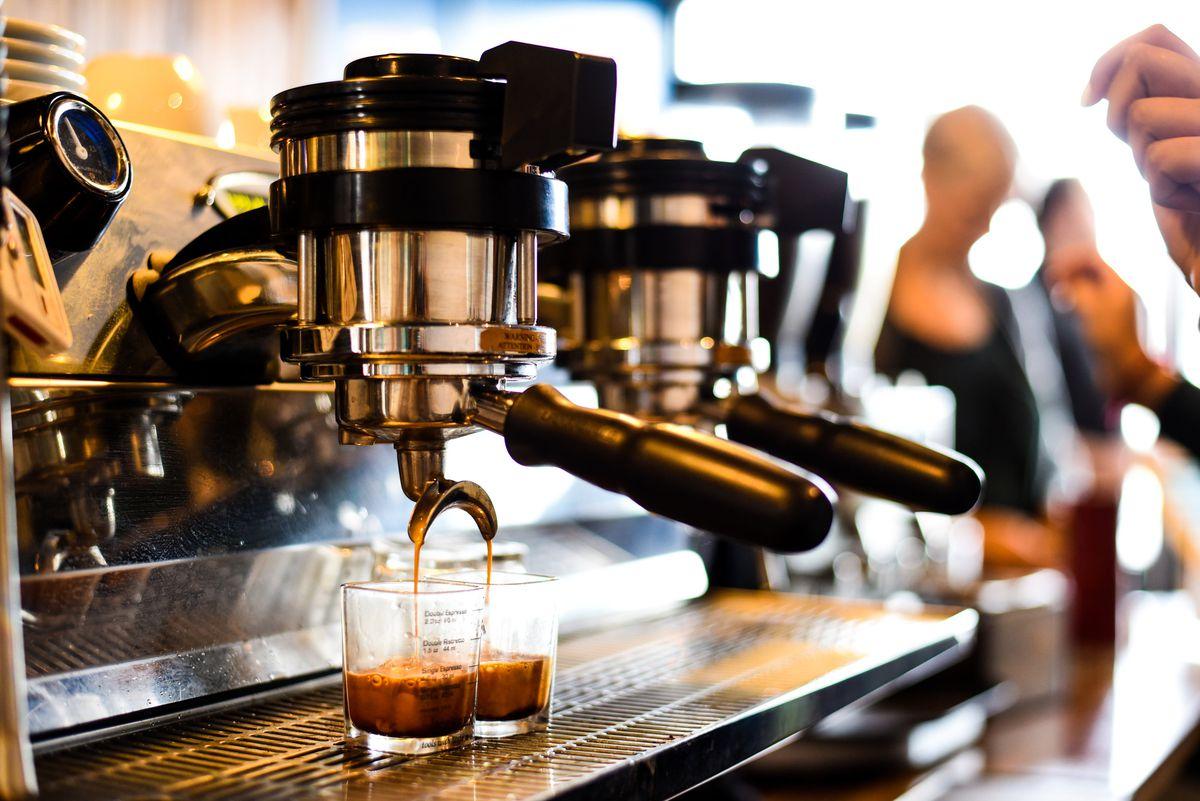 An espresso machine pulls light brown liquid into two small glasses.