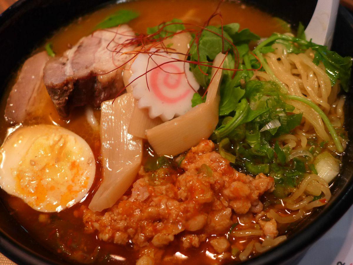 A ramen bowl bursting with bamboo shoots, egg, ground pork, and fishcake