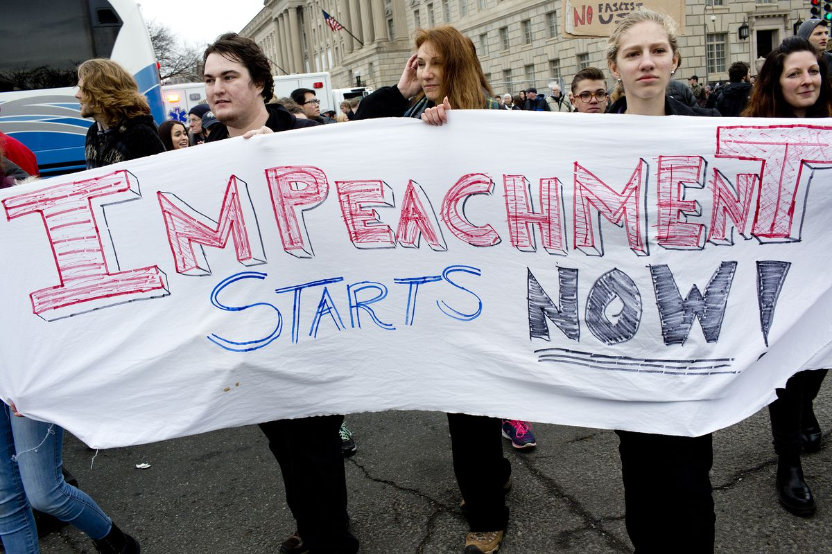Protesters hold a sign calling for President Trump's impeachment, on Inauguration Day.