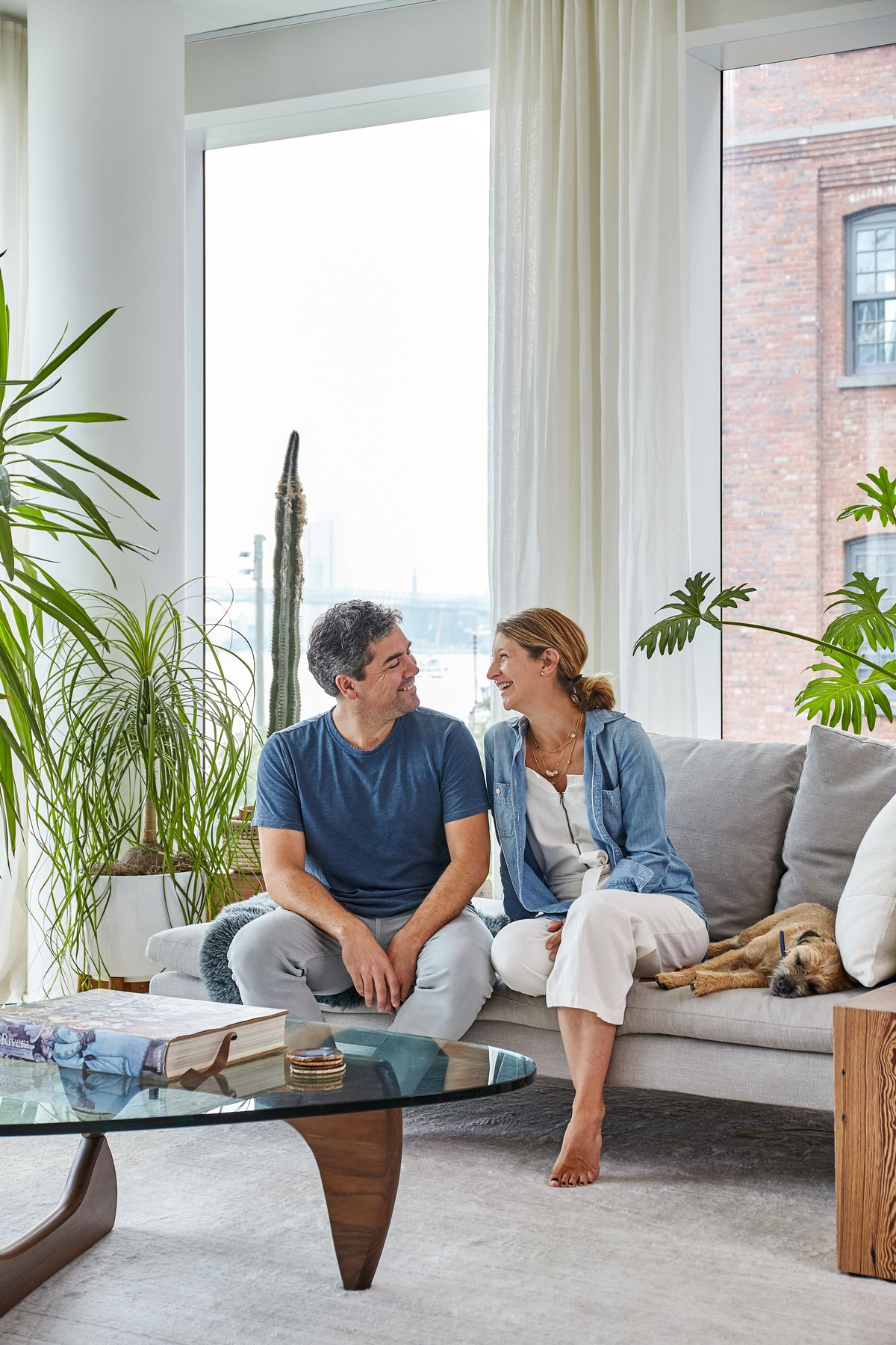 A man and a woman sit on a couch smiling and looking at each other. In the foreground is a glass table. In the background are plants in planters and floor to ceiling windows.