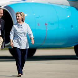 Democratic presidential candidate Hillary Clinton, right, accompanied by Democratic vice presidential candidate, Sen. Tim Kaine, D-Va., left, speak to each other as Clinton arrives at Cleveland Hopkins International Airport in Cleveland, Ohio, Monday, Sept. 5, 2016, after traveling from Westchester County Airport in White Plains, N.Y. (AP Photo/Andrew Harnik)