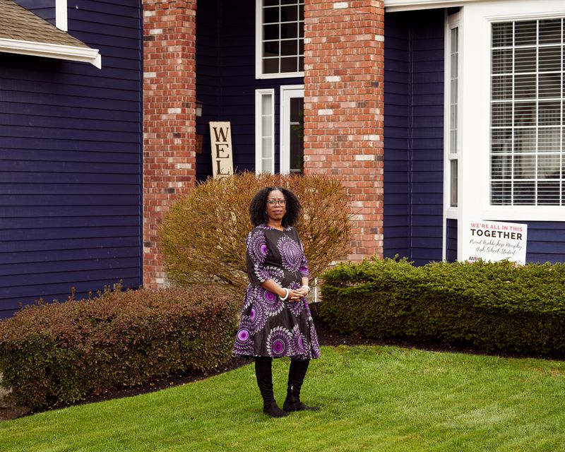 A woman in a print dress stands on the lawn of a house.