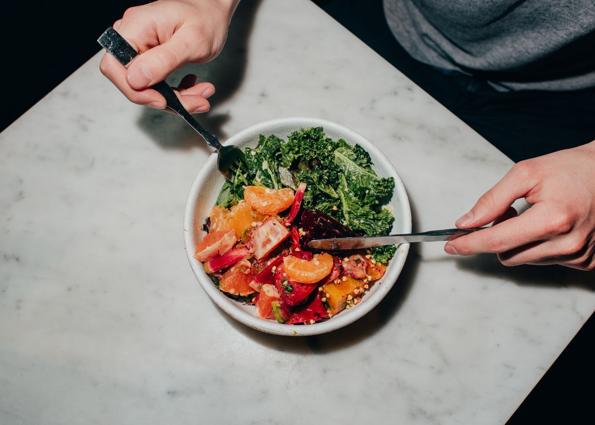 hands holding utensils in bowl of salad with greens and fruit
