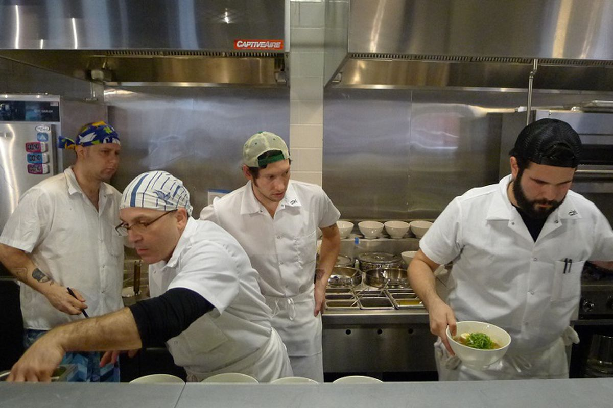 Four people stand behind a stainless steel countertop in a busy ramen restaurant