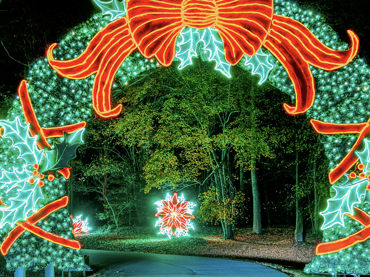 Christmas lights in the shape of a wreath over a road.