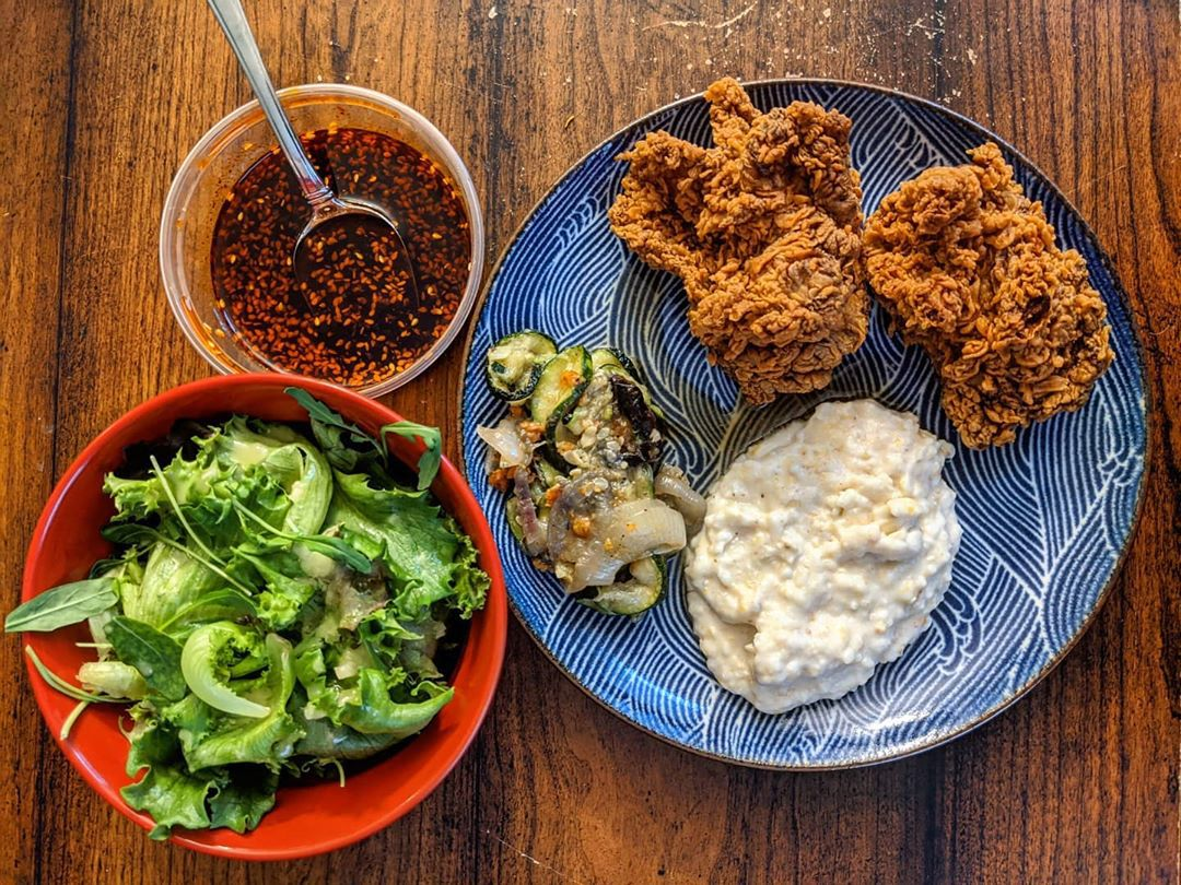 Overhead view of fried chicken, grits, and roasted zucchini on a blue plate. A red bowl of greens sits to the side, along with a plastic container of a red sauce. All sit on a wooden tabletop.