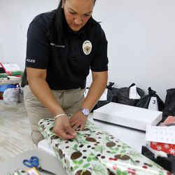West Valley City Sgt. Trudy Cropper wraps presents at the 13th annual Giving Tree program at Valley Fair Mall in West Valley City on Tuesday, Dec. 15, 2015. The program provides Christmas presents to 170 children from 61 low-income families in the city.