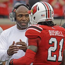 Louisville coach Charlie Strong, left, talks with cornerback Adrian Bushell (21) during a time out in their season-opening NCAA college football game at Cardinal Stadium in Louisville, Ky., Sunday, Sept. 2, 2012, against rival Kentucky. Louisville won 32-14.