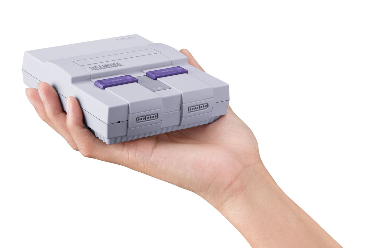 holding SNES Classic Edition in hand