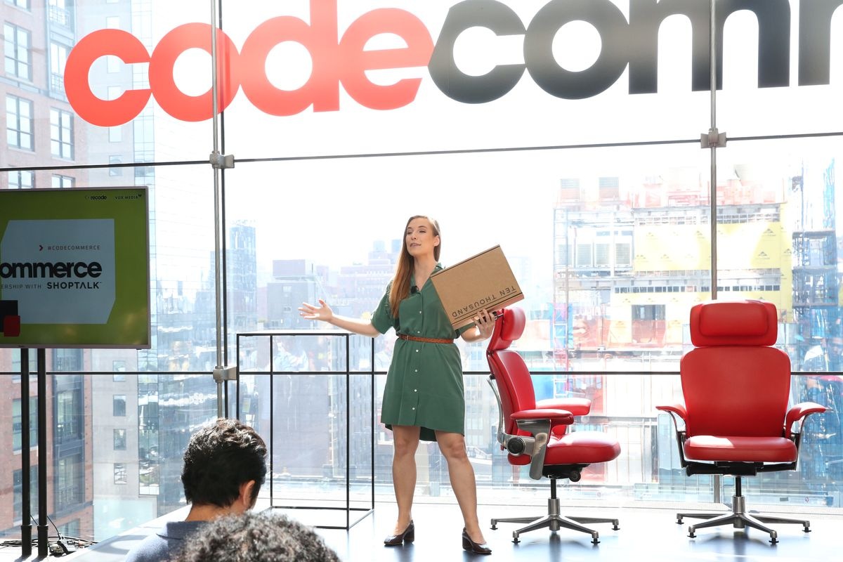 Lumi CEO Jesse Genet holds a cardboard box up to the crowd while speaking at Recode's Code Commerce conference in New York City.