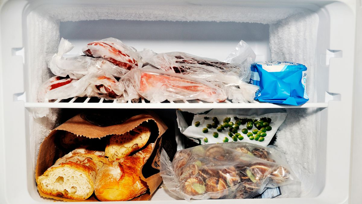 Freezer compartment of a refrigerator containing meat and frozen vegetables as well as bread.