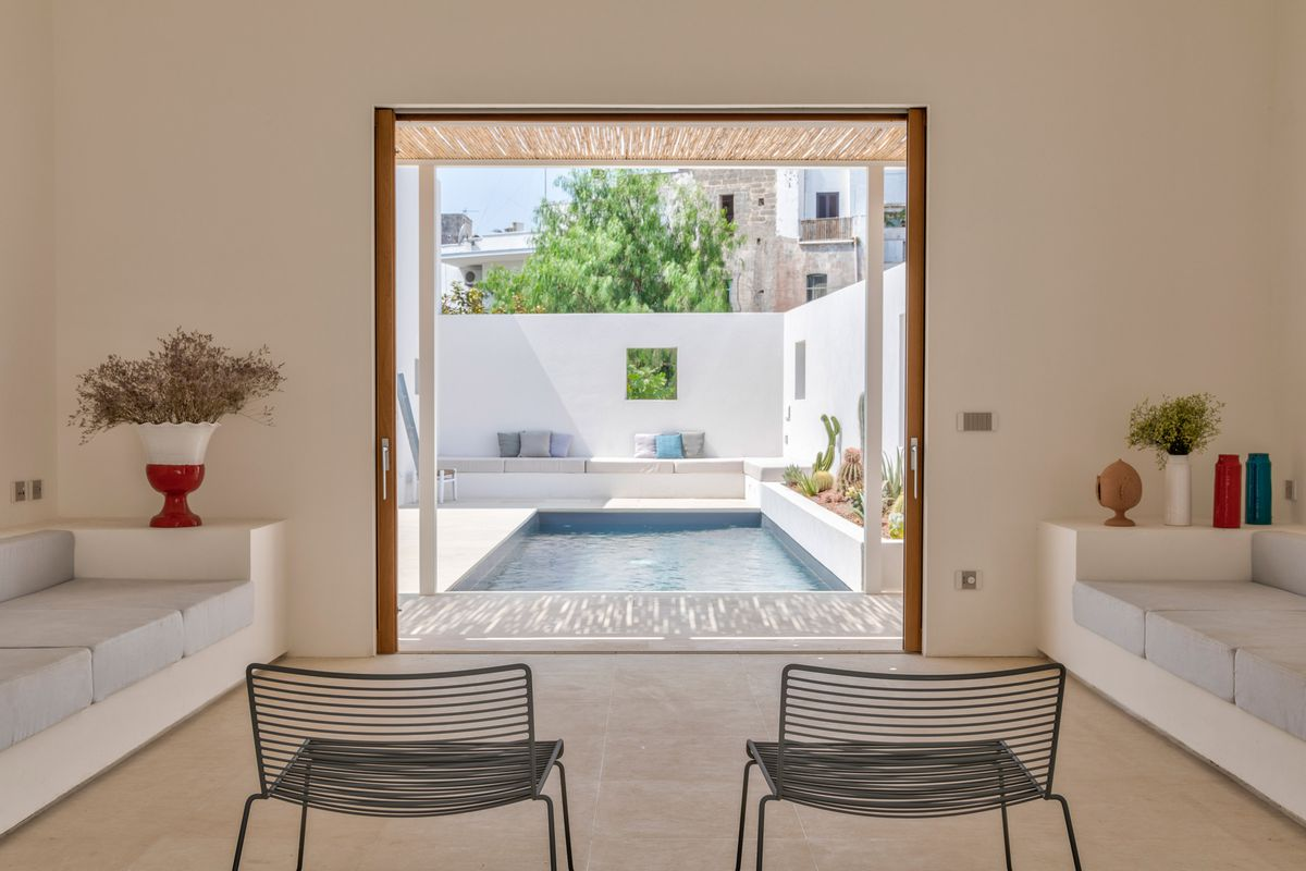 Two black chairs facing open door looking out onto pool.