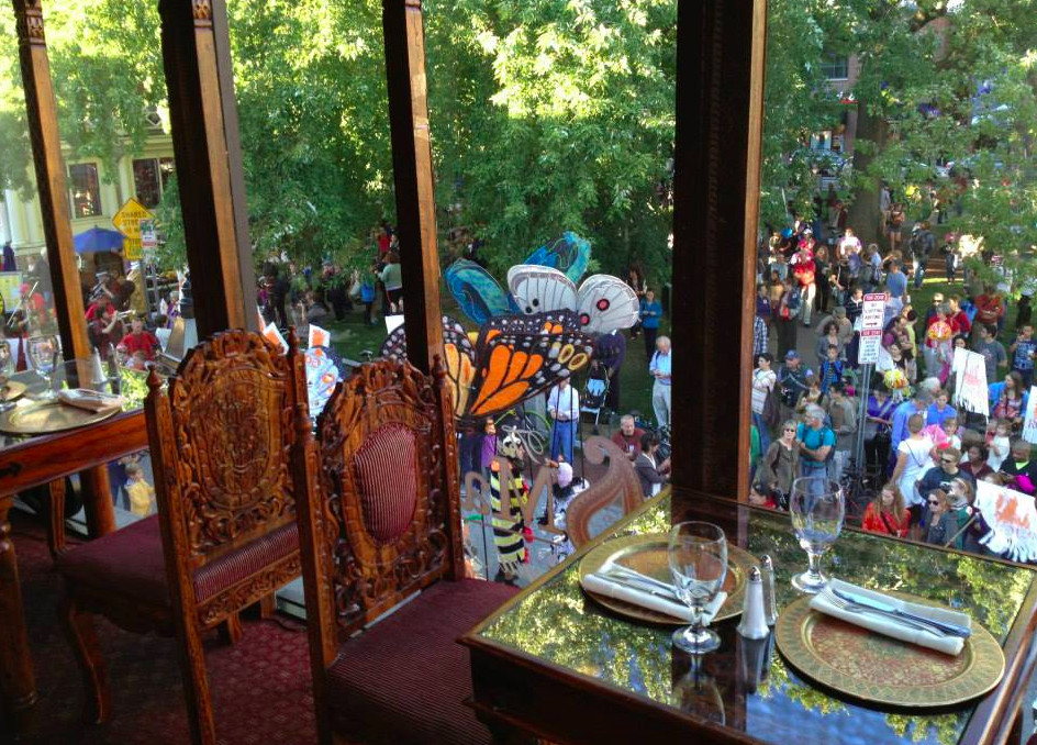 Two restaurant tables are set against a floor-to-ceiling window overlooking a park full of people and trees. The chairs at the tables are intricately carved wood in an artistic Indian style.