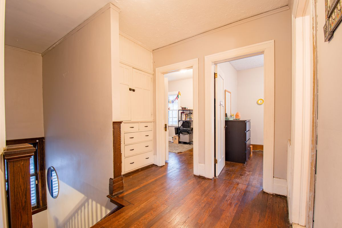The second-story landing has wood floors and white, built-in cabinets. Two open doors lead to two bedrooms.
