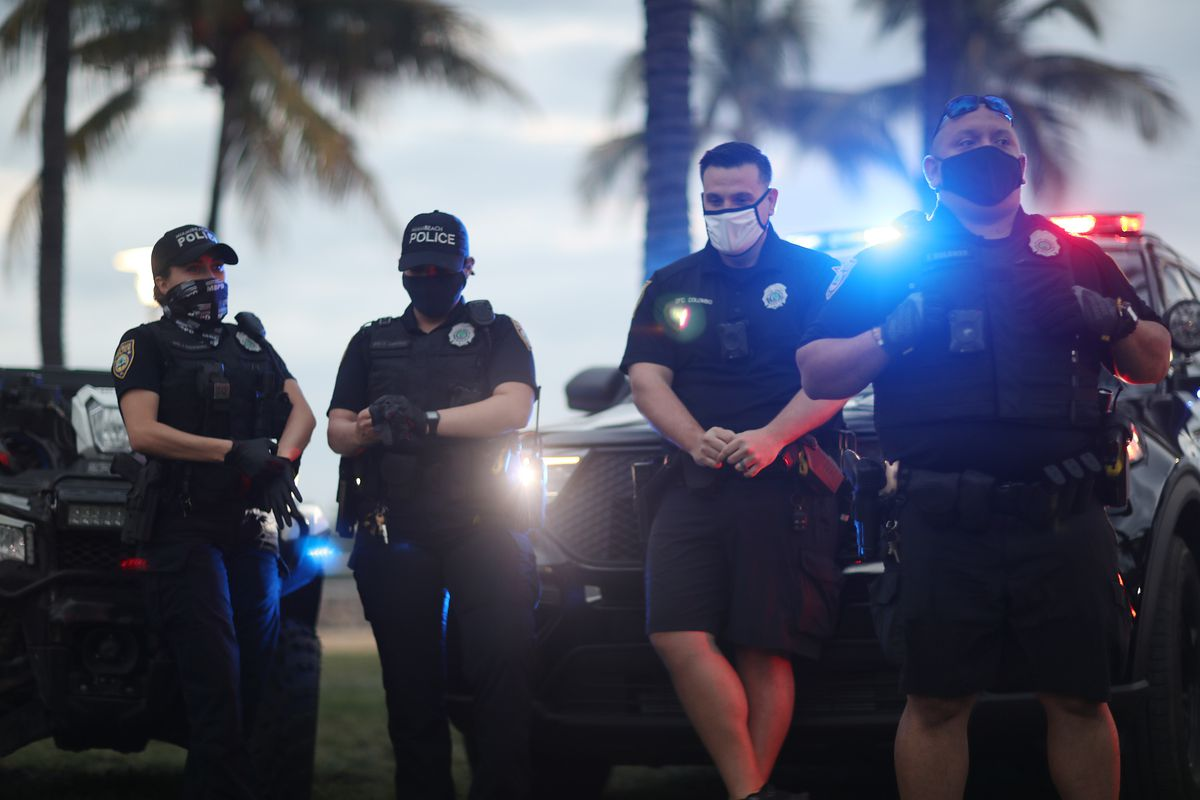 Four officers, two women and two men, stand in front of police cars with flashing lights. All are in navy blue uniforms, and all are wearing masks.