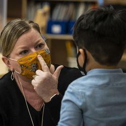 Preschool teacher Angela Panush shows a student how to keep his mask over his nose during class at Dawes Elementary School at 3810 W. 81st Pl. on the Southwest Side, Monday morning, Jan. 11, 2021.