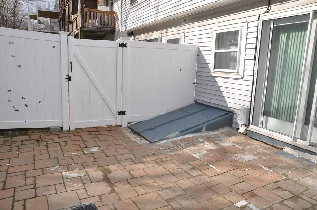 A small fenced-in patio with a closed cellar door.