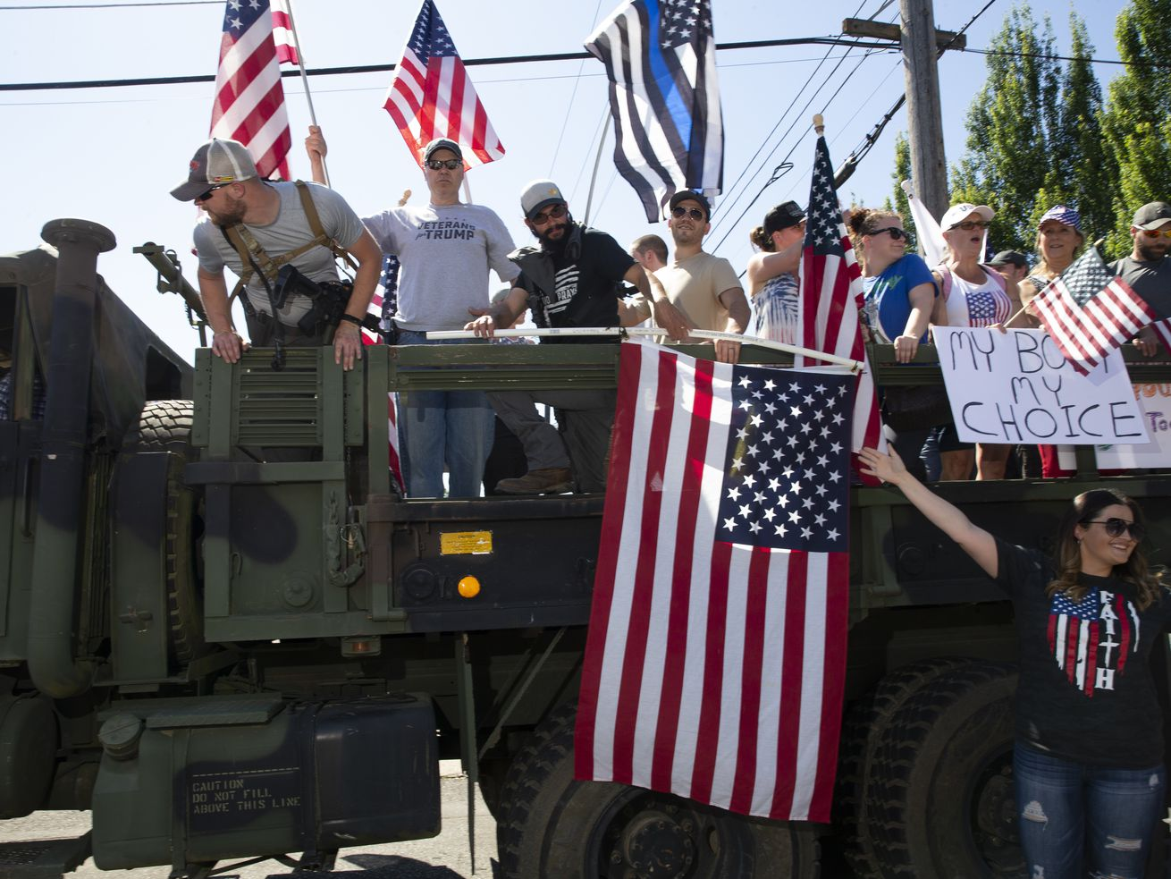 People in the back of a truck waving a flag and yelling in a protest.