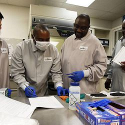 Michael Lin, left, a biotechnical solutions scientist at Sorenson Forensics, trains Andros Theo, Christopher Sakala and Katongo Chipompo in DNA amplification in Salt Lake City, Tuesday, Aug. 27, 2013.