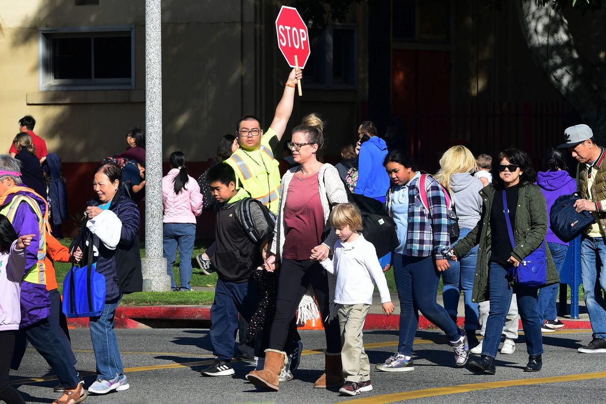 An Alhambra Unified School District crossing guard stops traffic for parents picking up their children from Ramona Elementary School on Feb. 4, 2020, in Alhambra, California. As the novel coronavirus outbreak spreads, fueling rumors and misinformation, an online petition to cancel classes in the  district had garnered more than 14,000 signatures. The petition on Change.org urges Alhambra Unified, east of Los Angeles and with a heavily Asian population, to shut down until the outbreak is over. Sc
