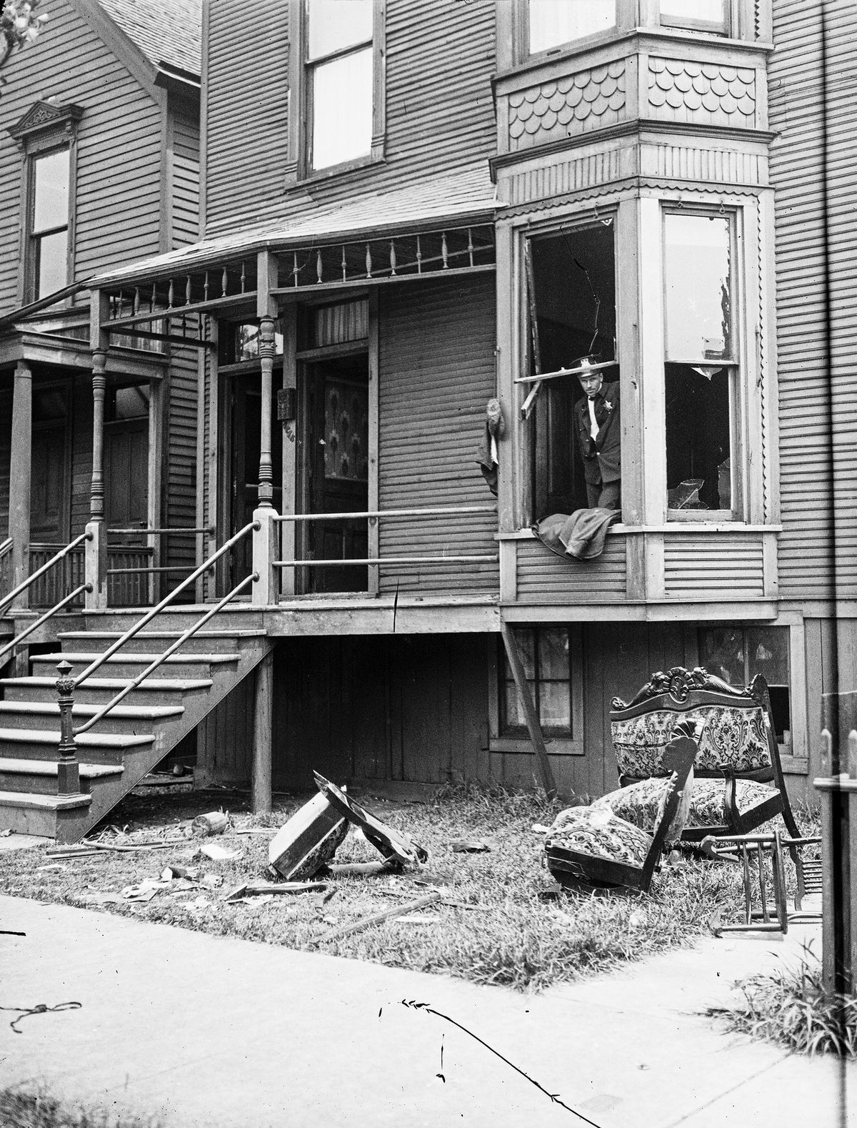 Police look through a broken window of a house during the 1919 race riots in Chicago.