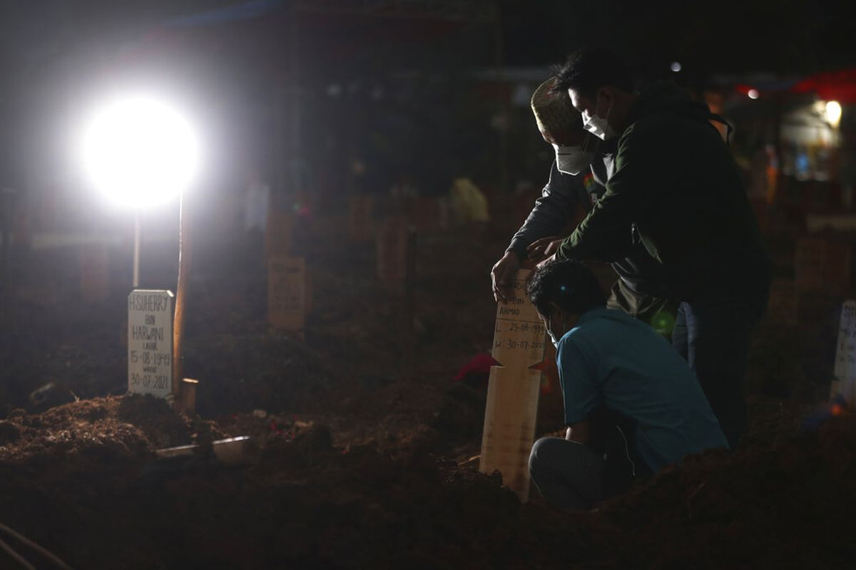 Family members react during the burial of their relative at during the coronavirus outbreak in Bekasi, West Java, Indonesia.