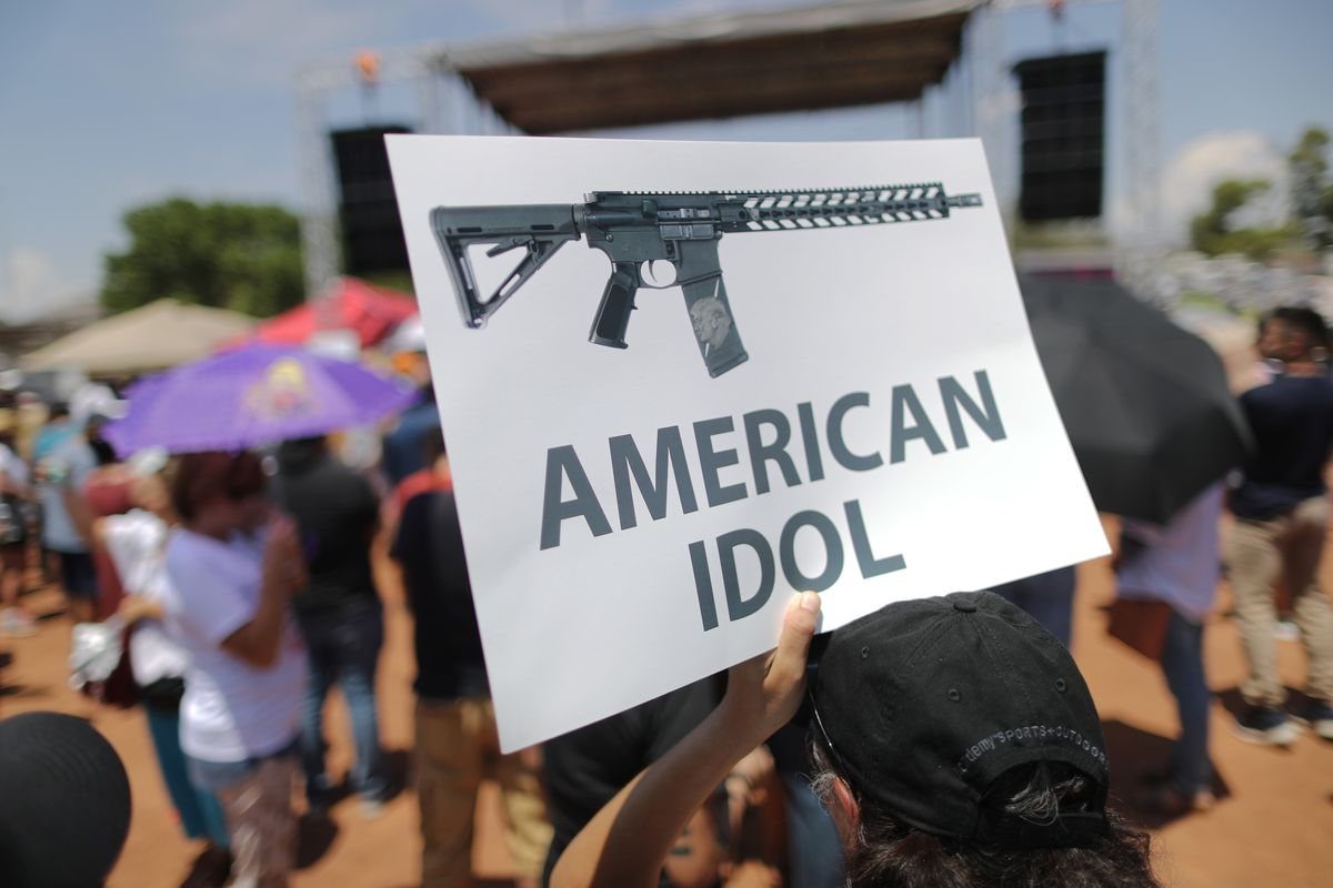 A demonstrator holds a sign depicting an assault rifle at a protest against President Trump's visit, following a mass shooting which left at least 22 people dead, on Aug. 7, 2019 in El Paso, Texas.