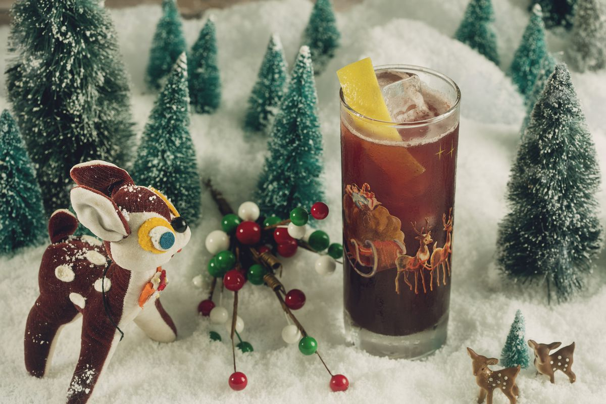 a cocktail in a tall chimney glass surrounded by vintage Christmas toys