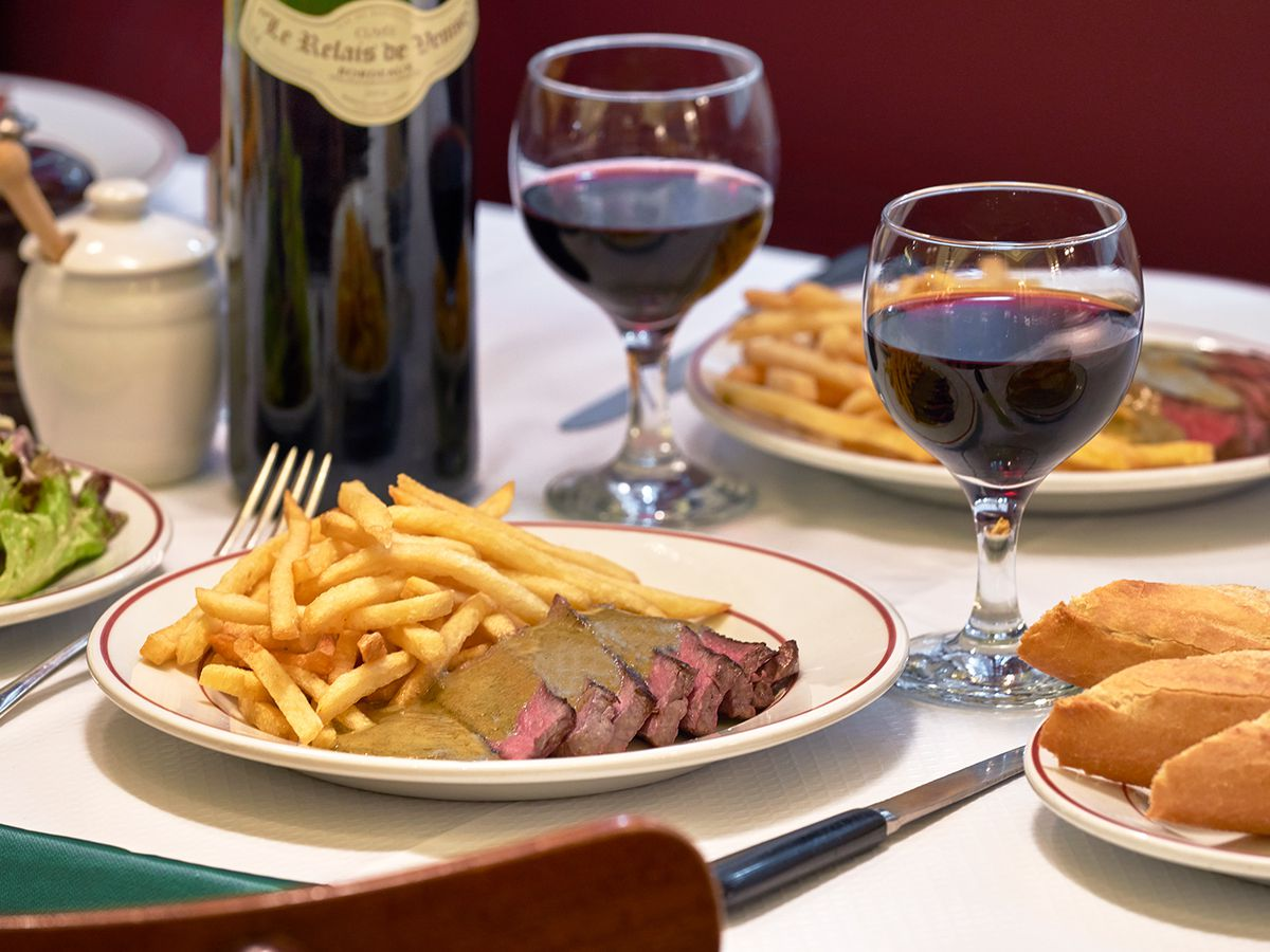 Steak frites and red wine on a table