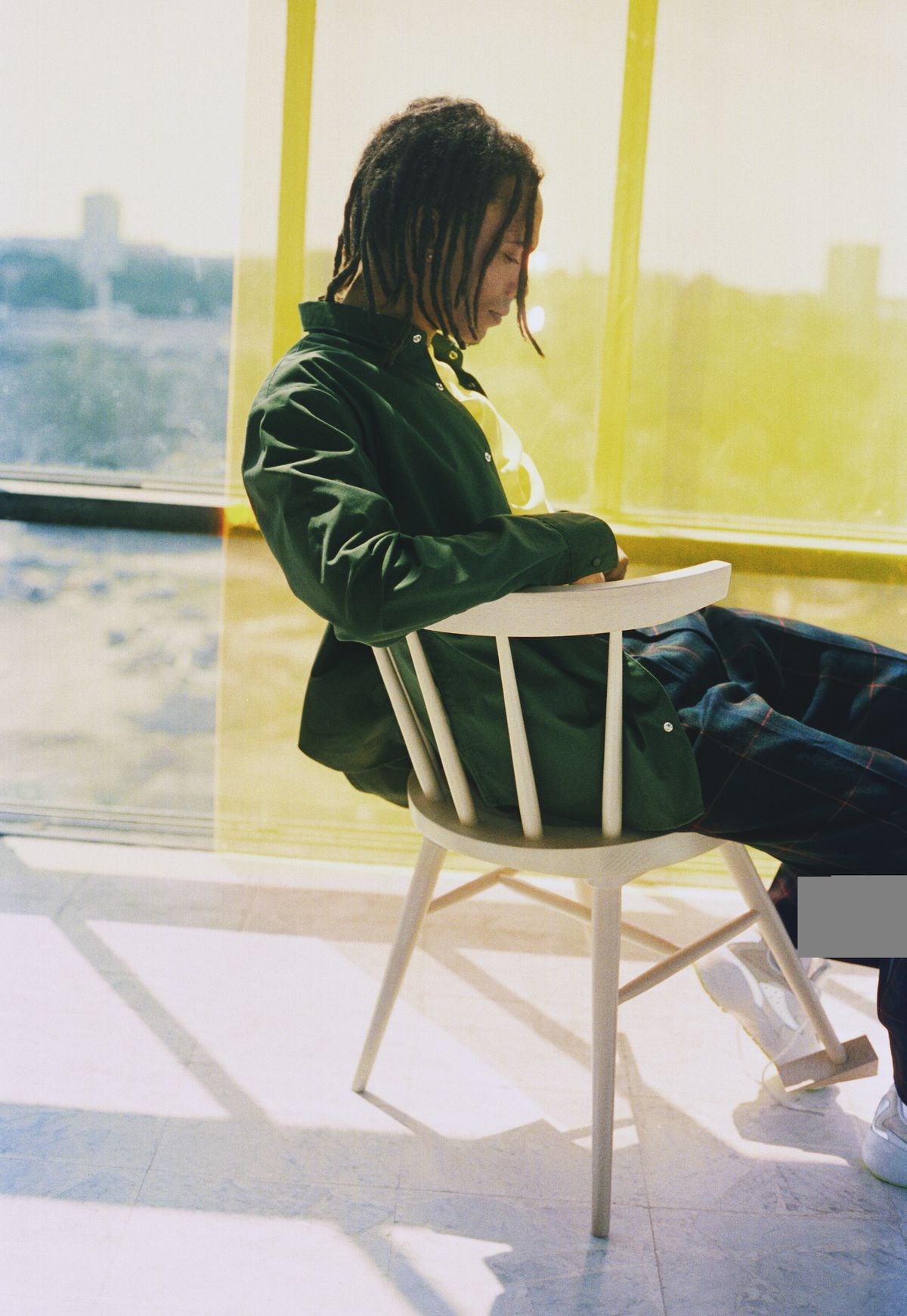 A man sits in a wooden chair with a doorstop forming one of the chair legs.