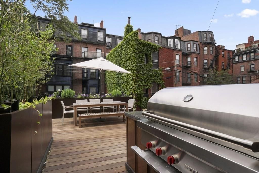 A deck, with a table and chairs and a grill, behind a townhouse.