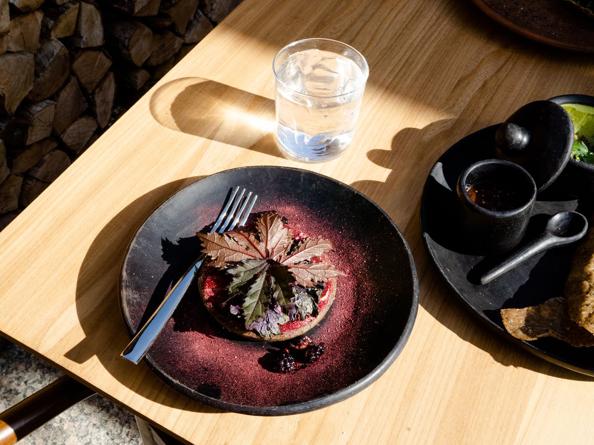 A dark plate with a masa cake topped in a large dark purple shiso leaf, dusted with a magenta powder