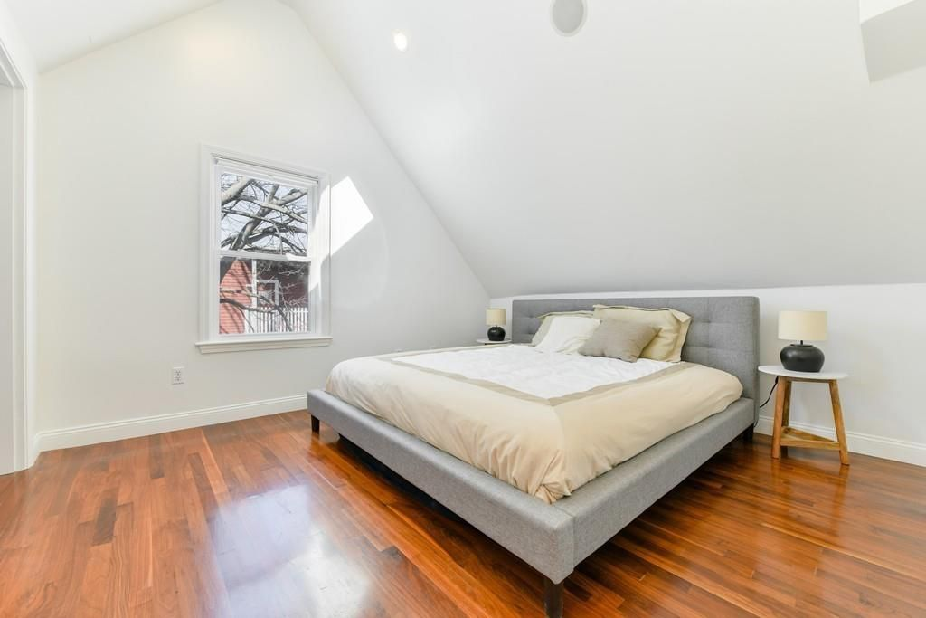 A bedroom with a bed and a peaked ceiling.