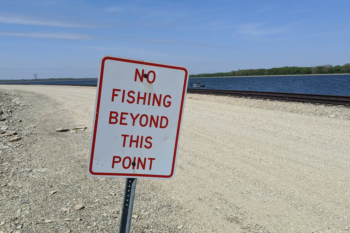 A sign of the times, the sign ending the bank fishing area on the center dike at Heidecke Lake is on tilt. Credit: Dale Bowman