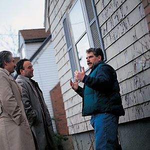<p>Dee confers with paint-company experts about the peeling paint.</p>