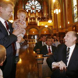 LDS Church President Thomas S. Monson talks with Scott Daw, holding his son, Brennan, prior to services Sunday.