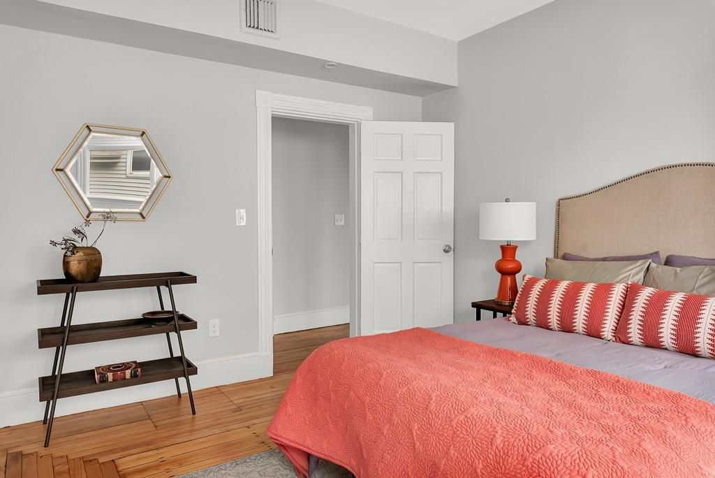 A bedroom with a bed, and the door is opened into the room.