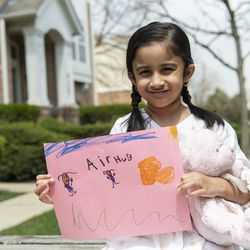 Maryam Rizvi, 5, holds up a drawing she made of herself giving an air hug, Tuesday, April 28, 2020.