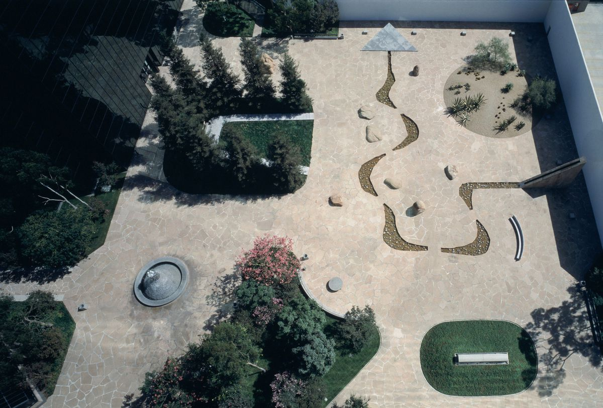 An aerial photograph of a sculpture garden, which has abstract geometric shapes, trees, and a flowing creek