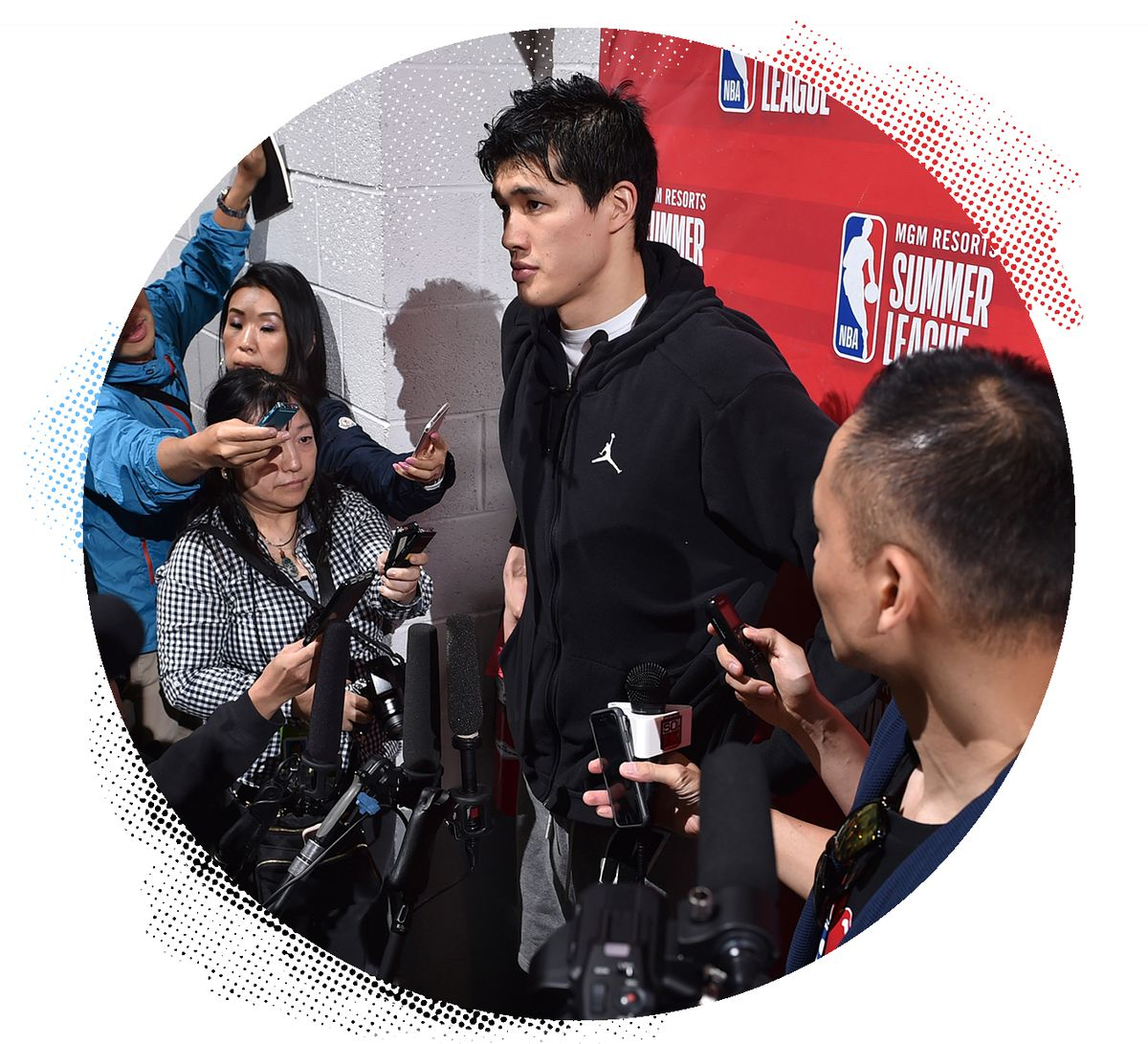 Yuta Watanabe stands in the middle of a group of reporters answering questions.