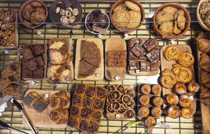 A tray of galettes, cookies, caneles, and tarts on a wire rack, at one of London's best bakeries, E5 Bakehouse
