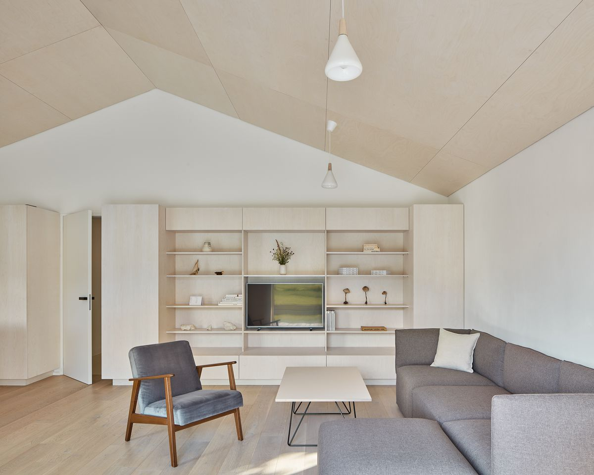 A white and beige living room with built-in storage shelving, gray furniture, and a white coffee table.