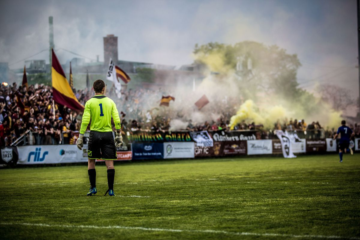 Detroit City FC in the backdrop of a cloud of smoke.