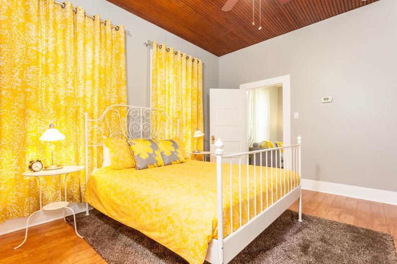 A bedroom with an exposed beadboard ceiling and wood floors. It has a bed with an iron frame and two metal nightstands against one wall. Walls are gray. The bed linens and curtains are patterned and dominated by bright yellow. An open door shows a couch w