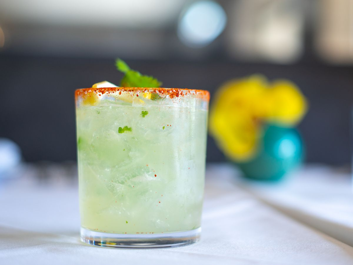 A vibrant green cocktail with spicy salted rim and an herbal garnish sitting on a table with a pot of flowers blurred in the back